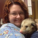 Jess is a pet advocate for PetCure Oncology and she's holding an opossum